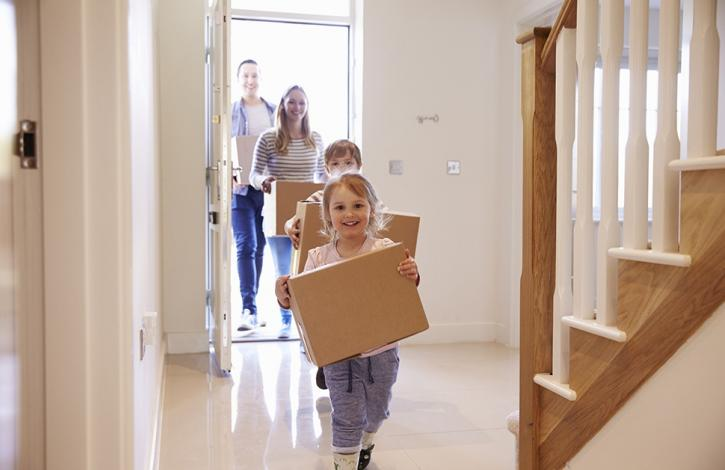 happy_family_carrying_moving_boxes_in